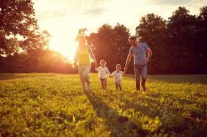 Happy children with parents running in park