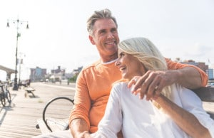 Man and woman sitting together on a beach boardwalk. Both are smiling. They are holding hands.