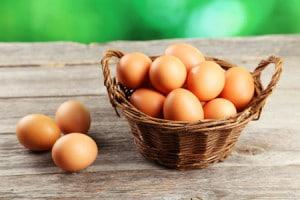 41530509 - chicken eggs in basket on grey wooden background
